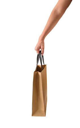 Female hand holding blank brown papaer shopping bags isolated on white background