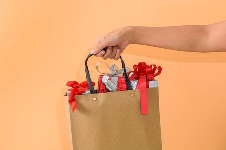 Female hand holding blank brown papaer shopping bags full of gift boxes ornamented on Orange background. with copy space for your message