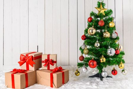 Christmas tree and ornaments with gifts boxes on white fur and white wooden background with copy space