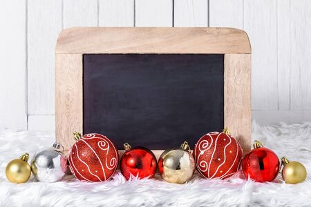 Close up Christmas ornaments and chalkboard on white fur and white wooden background