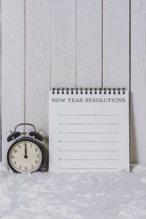 New Years Resolutions List written on Notebook with Alarm clock on white fur and white wooden background