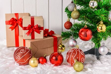 Close up Christmas tree and ornaments with gifts boxes on white fur and white wooden background Stok Fotoğraf