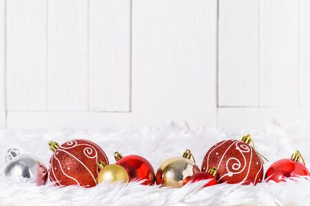 Close up Christmas ornaments on white fur and white wooden background