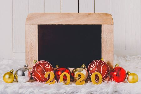 2020 wooden text with Christmas ornaments and chalkboard on white fur and white wooden background Stok Fotoğraf