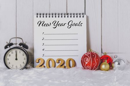 2020 wooden text with Alarm clock with Christmas ornaments and New Years Goals List written on Notebook with white fur and white wooden background