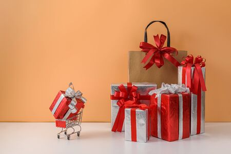 Paper shopping bags and shopping cart, trolley. many Gift Box with Red bow on white table and pastel orange background. with copy space for your message. Shopping New Years gift, Christmas Concept