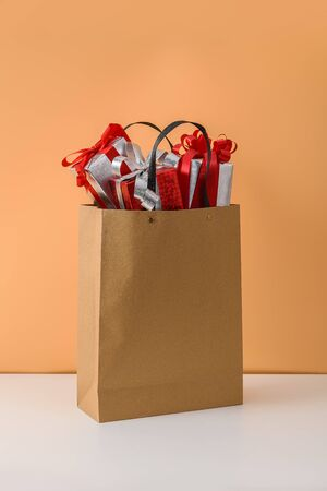 Many Gift Box with Red ribbon bow in Brown paper shopping bag on white table and pastel orange background. with copy space for your message and logo. concepts New Years gift or Christmas
