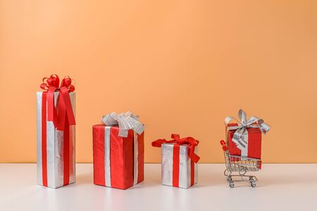 Many Gift Box with Red bow on shopping cart, trolley on white table and pastel orange background. with copy space for your message. The concept of selling shopping online, New Years gift or Christmas