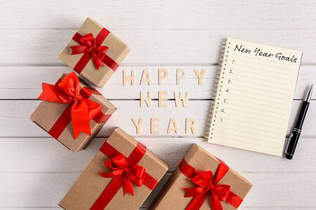 HAPPY NEW YEAR 2020 Wood New Years Goals List written on Notebook with gift box on white wooden background