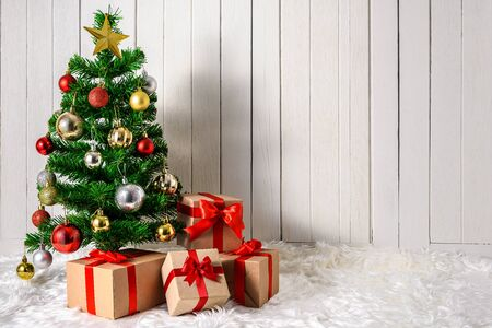 Christmas tree and ornaments with gifts boxes on white fur and white wooden background with copy space Stok Fotoğraf - 133089823