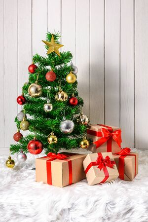 Christmas tree and ornaments with gifts boxes on white fur and white wooden background