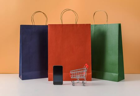 Paper shopping bags and shopping cart or trolley with smartphone on white table and pastel orange background. with copy space for your message and logo. The concept of selling or shopping online Stok Fotoğraf
