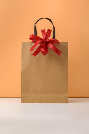 Mockup of blank craft package, Paper shopping bag with Red bow on white table and pastel orange background. with copy space for your message and logo. concepts New Years gift or Christmas