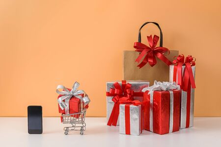 Paper shopping bags and shopping cart, many Gift Box with Red bow, smartphone on white table, orange background. Copy space for your message. Shopping online Christmas, News Year gift Concept