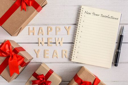 HAPPY NEW YEAR 2020 Wood New Years Resolutions List written on Notebook with gift box on white wooden background