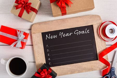 New Years Goals List written on chalkboard with gift box and smart phone, pen, coffee on white wooden background