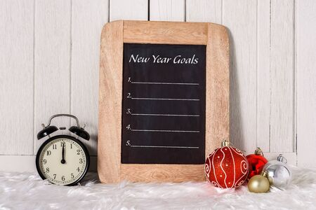 Alarm clock with Christmas ornaments and New Years Goals List written on chalkboard with white fur and white wooden background