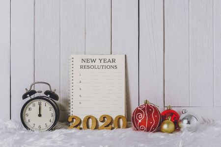2020 wooden text with Alarm clock with Christmas ornaments and New Years Resolutions List written on Notebook with white fur and white wooden background Stok Fotoğraf