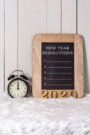 2020 wooden text and New Years Resolutions List written on Notebook with Alarm clock on white fur and white wooden background Stok Fotoğraf