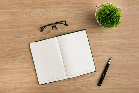 Top view office table desk. Flat lay Workspace with blank notebook, pen, eye glasses, tree pot office supplies on wooden table background. Stok Fotoğraf - 133545965