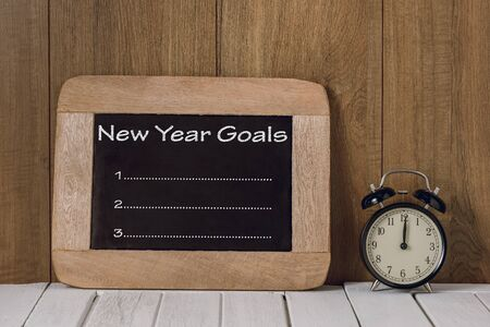 New Years Goals List written on chalkboard with Alarm clock over wooden background Stok Fotoğraf