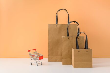 Paper shopping bags and shopping cart or trolley on white table and pastel orange background. with copy space for your message and logo. The concept of selling or shopping online