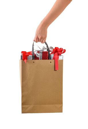 Female hand holding blank brown papaer shopping bags full of gift boxes ornamented isolated on white background with clipping path