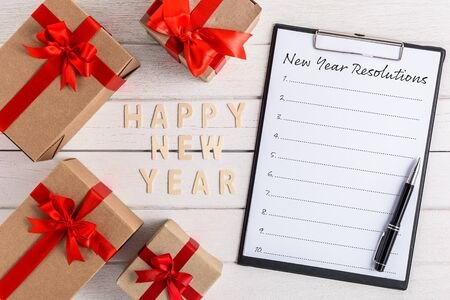 HAPPY NEW YEAR 2020 Wood New Years Resolutions List written on clipboard with gift box on white wooden background Imagens