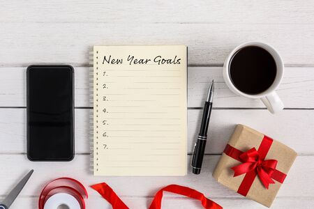 New Years Goals List written on Notebook with gift box and smart phone, pen, coffee on white wooden background