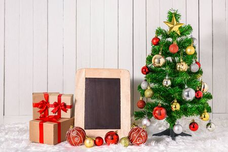 Christmas tree and ornaments with gifts boxes and chalkboard on white fur and white wooden background with copy space Stok Fotoğraf