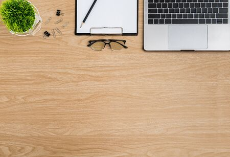 Top view Wood office desk table. Flat lay Workspace with eye glasses, tree pot, keyboard, laptop, paper clip, clipboard, notebook, pencil office supplies on wooden table background