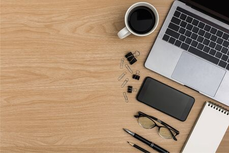 Top view Wood office desk table. Flat lay Workspace with eye glasses, smart phone, coffee cup, laptop, paper clip, notebook, pencil, pen office supplies on wooden background