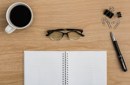Top view office table desk. Flat lay Workspace with blank notebook, coffee cup, pen, paper clip, eye glasses office supplies on wooden table background. Imagens