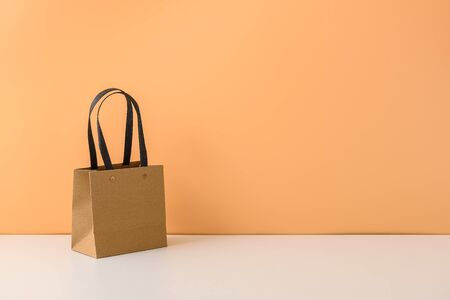 mockup of blank craft package or Brown paper shopping bag with handles on white table and pastel orange background. with copy space for your message and logo