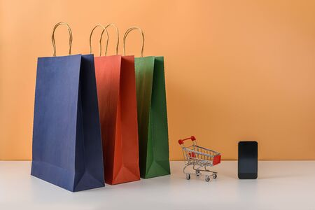 Paper shopping bags and shopping cart or trolley with smartphone on white table and pastel orange background. with copy space for your message and logo. The concept of selling or shopping online Imagens