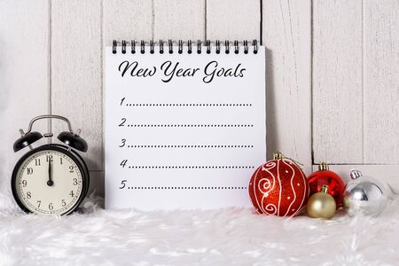 Alarm clock with Christmas ornaments and New Years Goals List written on Notebook with white fur and white wooden background Imagens