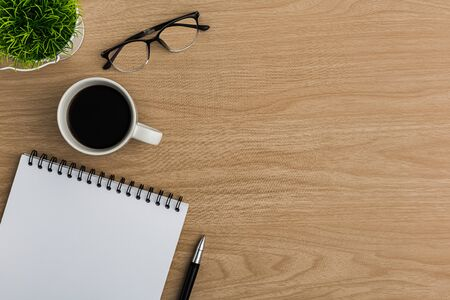 Top view office table desk. Flat lay Workspace with blank notebook, pen, eye glasses, tree pot, coffee cup office supplies on wooden table background.