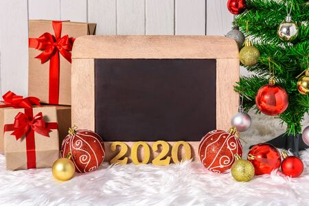 2020 wooden text with Christmas tree and ornaments with gifts boxes and chalkboard on white fur and white wooden background with copy space
