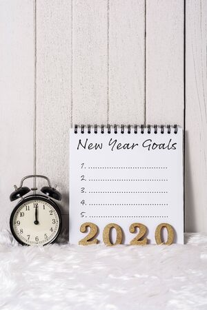 2020 wooden text and New Years Goals List written on Notebook with Alarm clock on white fur and white wooden background