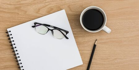 Top view office table desk. Flat lay Workspace with blank notebook, coffee cup, pencil, eye glasses office supplies on wooden table background.