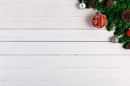 Christmas fir tree with decoration on white wooden board. Top view with copy space Imagens