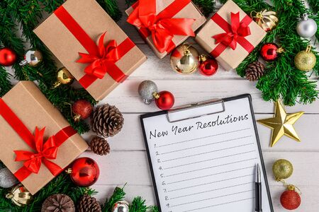 New Years Resolutions List written on white paper on clipboard with Christmas fir tree and decoration on white wooden board. Top view with copy space. Christmas or New year background Imagens