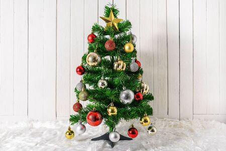 Christmas tree and ornaments on white fur and white wooden background with copy space