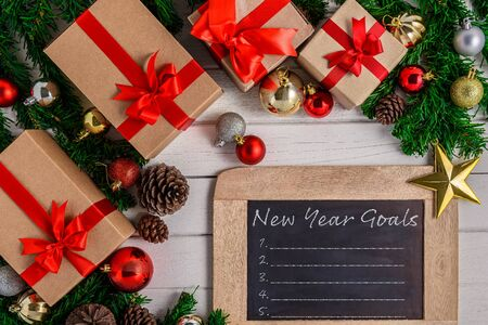 New Years Goals List written on chalkboard with Christmas fir tree and decoration on white wooden board. Top view with copy space. Christmas or New year background Stok Fotoğraf