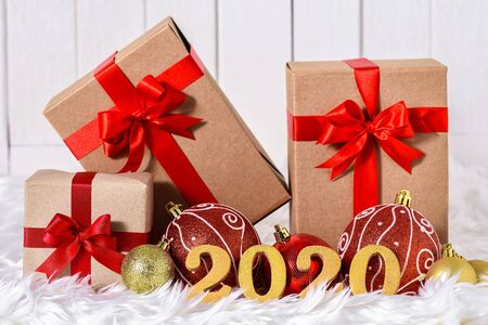 2020 wooden text with Close up Christmas ornaments with gifts boxes on white fur and white wooden background Stok Fotoğraf