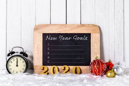 2020 wooden text with Alarm clock with Christmas ornaments and New Years Goals List written on chalkboard with white fur and white wooden background