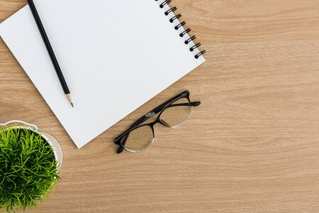 Top view office table desk. Flat lay Workspace with blank notebook, coffee cup, pencil, eye glasses, tree pot office supplies on wooden table background.
