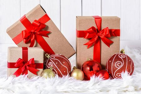 Close up Christmas ornaments with gifts boxes on white fur and white wooden background