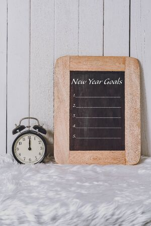 New Years Goals List written on Notebook with Alarm clock on white fur and white wooden background
