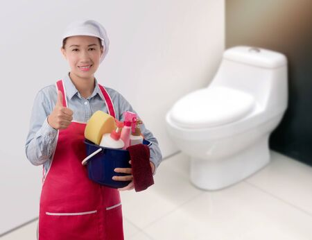 Cleaning concept Woman with bucket of washing fluids and rags in hands and cleaning equipment ready to clean house on blurred toilet background